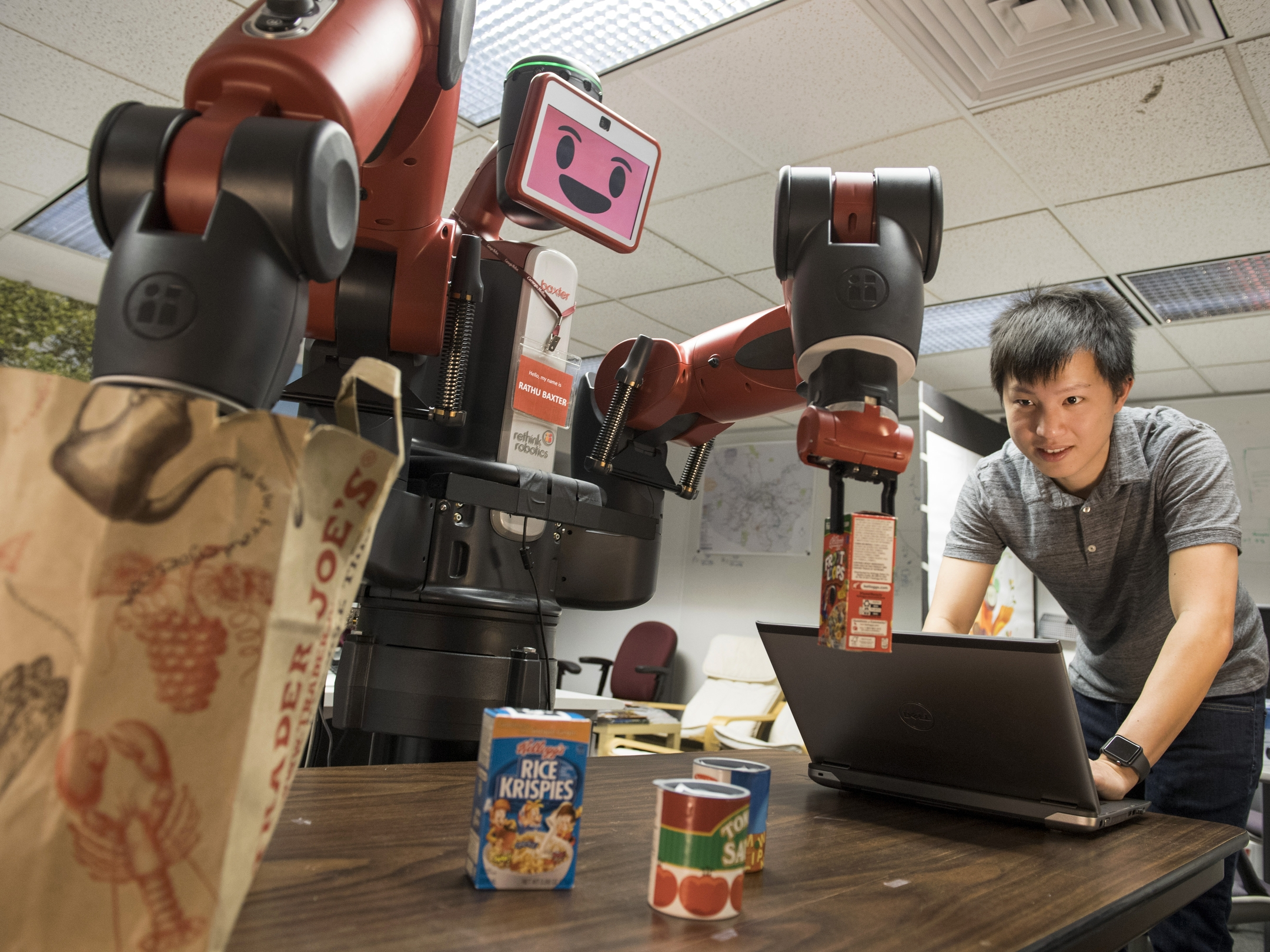 Photo of Xiang Zhi Tan, a Ph.D. student in the Robotics Institute, works with a Baxter robot, part of a multi-university research program to enable robots to assess their own performance at tasks.