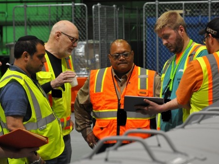 "The Robotics Institute's David Kohanbash, principal systems/software engineer, and William ""Red"" Whittaker, professor of robotics, discuss how a tablet can be used to launch the RadPiper uranium-detection robot with Rodrigo V. Rimando Jr., director of technology development for DOE's Office of Environmental Management, and Charles Allyn, a non-destructive assay technician with Fluor-BWXT Portsmouth."