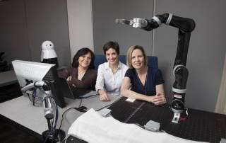 Anita Woolley, Cleotilde Gonzalez and Henny Admoni posing for a group photo in lab with robotics arm